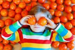 Peu de garçon d'enfant avec les mandarines saines porte des fruits Images libres de droits