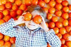 Peu de garçon d'enfant avec les mandarines saines porte des fruits Photo stock
