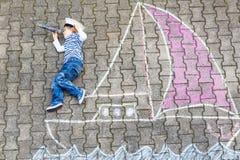Peu de garçon d'enfant ayant l'amusement avec le dessin de photo de bateau avec la craie Images stock