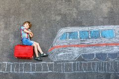 Peu de garçon d'enfant ayant l'amusement avec le dessin de photo de train rapide avec les craies colorées sur l'asphalte Images libres de droits