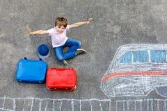 Peu de garçon d'enfant ayant l'amusement avec le dessin de photo de train rapide avec les craies colorées sur l'asphalte Photo stock