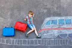 Peu de garçon d'enfant ayant l'amusement avec le dessin de photo de train rapide avec les craies colorées sur l'asphalte Images stock