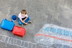 Peu de garçon d'enfant ayant l'amusement avec le dessin de photo de train rapide avec les craies colorées sur l'asphalte Photos stock