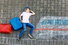 Peu de garçon d'enfant ayant l'amusement avec le dessin de photo de train rapide avec les craies colorées sur l'asphalte Image stock