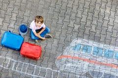 Peu de garçon d'enfant ayant l'amusement avec le dessin de photo de train rapide avec les craies colorées sur l'asphalte Photographie stock