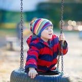 Peu de garçon d'enfant ayant l'amusement sur l'oscillation à chaînes dehors Image stock