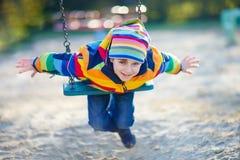 Peu de garçon d'enfant ayant l'amusement sur l'oscillation à chaînes dehors Image libre de droits