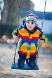 Peu de garçon d'enfant ayant l'amusement sur l'oscillation à chaînes dehors Photos libres de droits