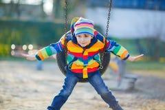 Peu de garçon d'enfant ayant l'amusement sur l'oscillation à chaînes dehors Photographie stock libre de droits