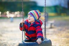 Peu de garçon d'enfant ayant l'amusement sur l'oscillation à chaînes dehors Photo stock