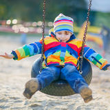 Peu de garçon d'enfant ayant l'amusement sur l'oscillation à chaînes dehors Photo libre de droits
