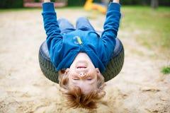 Peu de garçon d'enfant ayant l'amusement sur l'oscillation en été Photographie stock libre de droits