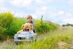 Peu de garçon d'enfant conduisant la grande voiture de jouet avec un ours, dehors image stock