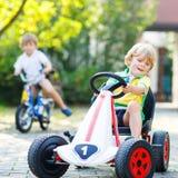 Peu de garçon d'enfant conduisant la voiture de pédale dans le jardin d'été Photos libres de droits