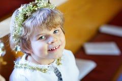 Peu de garçon d'enfant dans l'église le réveillon de Noël Photos stock