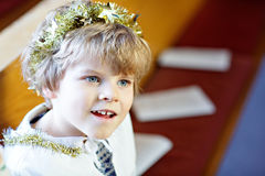 Peu de garçon d'enfant dans l'église le réveillon de Noël Photo stock