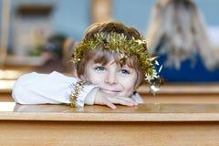 Peu de garçon d'enfant dans l'église le réveillon de Noël Image stock
