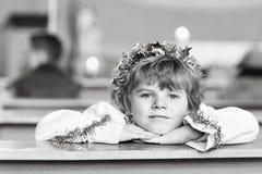 Peu de garçon d'enfant dans l'église le réveillon de Noël Photographie stock libre de droits