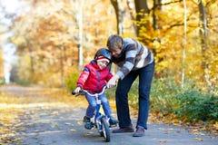 Peu de garçon d'enfant et son père en automne se garent avec une bicyclette Papa enseignant son faire du vélo de fils Photographie stock