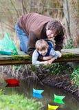 Peu de garçon d'enfant et son papa jouant ainsi que le papier coloré Photo stock