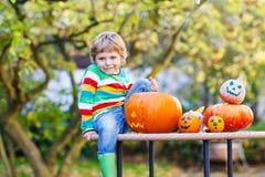 Peu de garçon d'enfant faisant la cric-o-lanterne pour Halloween dans l'orphie d'automne Photographie stock