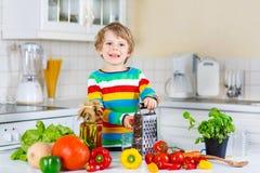 Peu de garçon d'enfant faisant la salade avec des légumes Photo libre de droits