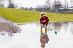 Peu de garçon d'enfant jouant avec le bateau de papier par le magma photo libre de droits