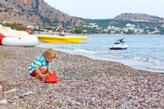 Peu de garçon d'enfant jouant sur la plage avec des pierres Image stock