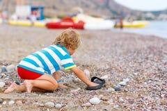 Peu de garçon d'enfant jouant sur la plage avec des pierres Photo stock