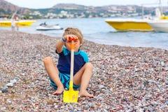 Peu de garçon d'enfant jouant sur la plage avec des pierres Photographie stock libre de droits