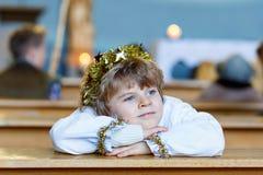 Peu de garçon d'enfant jouant un ange d'histoire de Noël dans l'église Photographie stock libre de droits