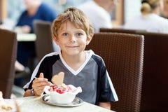 Peu de garçon d'enfant mangeant la crème glacée dans le café ou le restaurant extérieur Images libres de droits