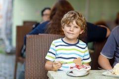 Peu de garçon d'enfant mangeant la crème glacée dans le café ou le restaurant extérieur Photo libre de droits