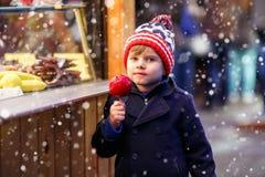 Peu de garçon d'enfant mangeant la pomme crystalized sur le marché de Noël Image libre de droits