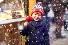 Peu de garçon d'enfant mangeant la pomme crystalized sur le marché de Noël Images libres de droits