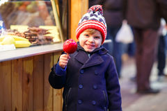 Peu de garçon d'enfant mangeant la pomme crystalized sur le marché de Noël Photographie stock libre de droits