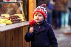 Peu de garçon d'enfant mangeant la pomme crystalized sur le marché de Noël Image stock