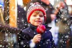 Peu de garçon d'enfant mangeant la pomme douce sur le marché de Noël Image stock