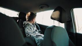 Peu de garçon d'enfant monte la chaise d'enfant dans l'automobile banque de vidéos