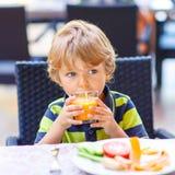 Peu de garçon d'enfant prenant le petit déjeuner sain dans le restaurant Photos stock