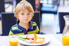Peu de garçon d'enfant prenant le petit déjeuner sain dans le restaurant Photo libre de droits