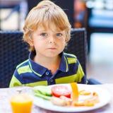 Peu de garçon d'enfant prenant le petit déjeuner sain dans le restaurant Photo stock