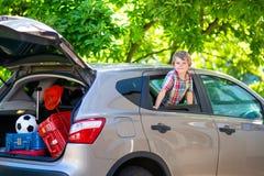Peu de garçon d'enfant s'asseyant dans la voiture juste avant partir pour des vacances Image stock