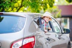 Peu de garçon d'enfant s'asseyant dans la voiture juste avant partir pour des vacances Images stock