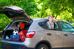 Peu de garçon d'enfant s'asseyant dans la voiture juste avant partir pour des vacances Photo stock