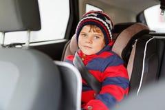 Peu de garçon d'enfant s'asseyant dans le siège de voiture de sécurité pendant le voyage photo stock