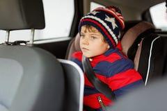 Peu de garçon d'enfant s'asseyant dans le siège de voiture de sécurité pendant le voyage photos stock