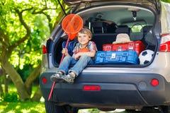 Peu de garçon d'enfant s'asseyant dans le tronc de voiture juste avant partir pour le vaca Photo libre de droits