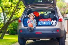 Peu de garçon d'enfant s'asseyant dans le tronc de voiture juste avant partir pour le vaca Image stock