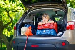 Peu de garçon d'enfant s'asseyant dans le tronc de voiture juste avant partir pour le vaca Images stock